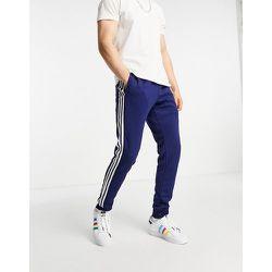 Adicolor - Jogger à trois bandes - Bleu - adidas Originals - Modalova